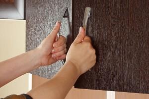 Women's hands are open cupboard doors dark wood